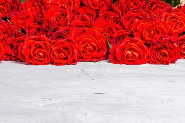 Luxuriöser strauß frischer roter rosen. das festliche konzept für hochzeiten, geburtstage, 8. märz, mutter- oder valentinstag. grußkarte, weiße holztafeln