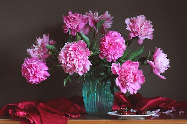 Luxuriöses bouquet aus rosa pfingstrosen und kirschen