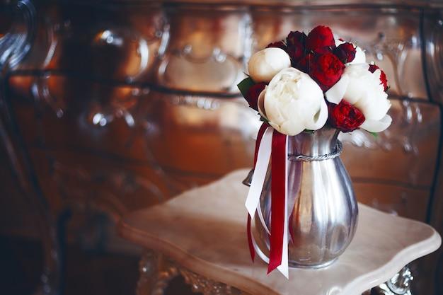 Luxuriöses bouquet von roten und weißen pfingstrosen in einer vase. warm toning