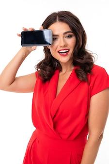 Luxuriöses brünettes mädchen in einem roten kleid mit einem telefon mit modell in ihren händen auf weiß