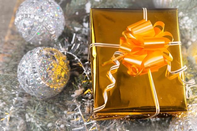 Luxuriöses dekoratives goldenes weihnachtsgeschenk mit goldenem band und schleife, eingebettet in ein bett aus silbernem lametta mit kugeln, erhöhte ansicht