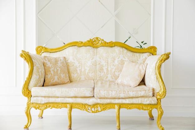 Luxuriöses goldenes sofa auf einem hintergrund der alten weißen wand.
