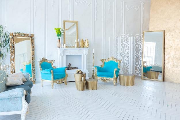 Luxuriöses helles interieur des wohnzimmers mit goldener wand und schicken teuren möbeln in den farben weiß und gold