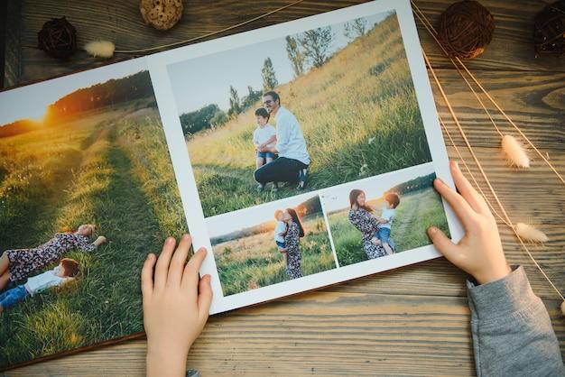Luxuriöses hölzernes fotobuch auf natürlichem hintergrund. familienerinnerungen fotobuch. speichern sie ihre sommerferienerinnerungen.