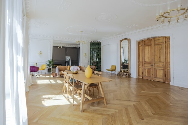 Luxuriöses interieur einer geräumigen wohnung in einem alten historischen haus aus dem 19. jahrhundert mit modernen möbeln. hohe decke und wände sind mit stuck verziert