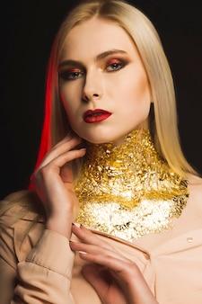 Luxuriöses model mit hellem abend-make-up und goldfolie am hals