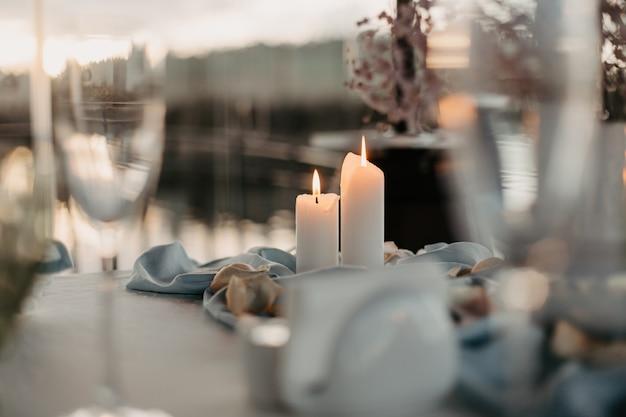 Luxuriöses romantisches candle-light-dinner für paare tischeinrichtung mit kerzen und rosenblättern in der nacht valentinstag dekoration