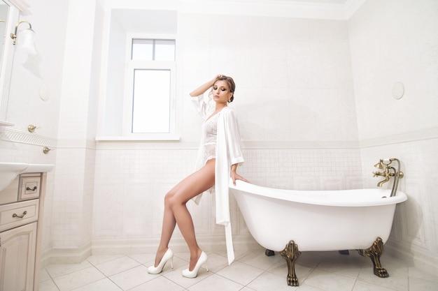 Luxuriöses schönes junges glückliches mädchen in weißer unterwäsche und einem morgenmantel im badezimmerdesign