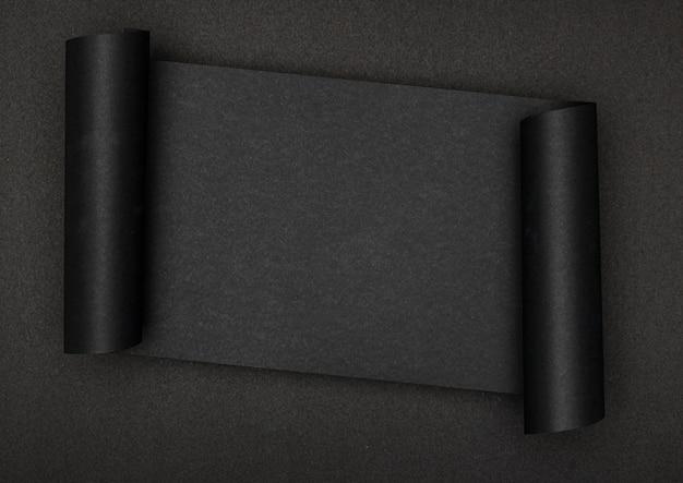 Luxuriöses schwarzes stück papier auf schwarzem hintergrund