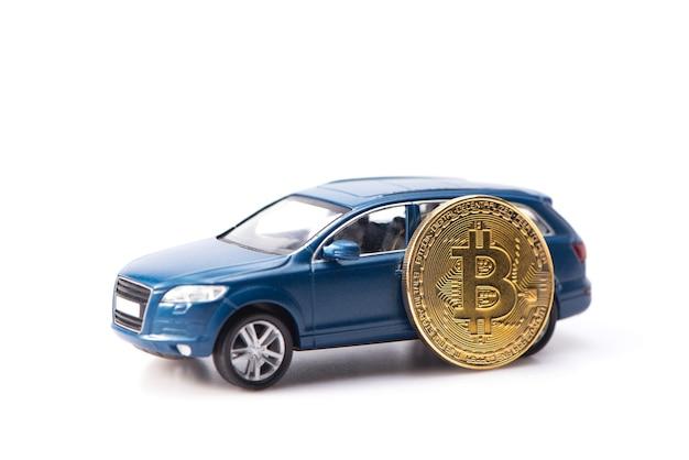 Luxuriöses und teures blaues geländewagen-spielzeugauto, das dank der bitcoin-kryptowährung gekauft wurde. auf weißem hintergrund isoliert.