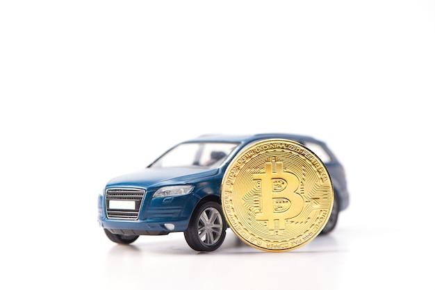 Luxuriöses und teures blaues geländewagen-spielzeugauto, das dank der bitcoin-kryptowährung gekauft wurde. auf weißem hintergrund.