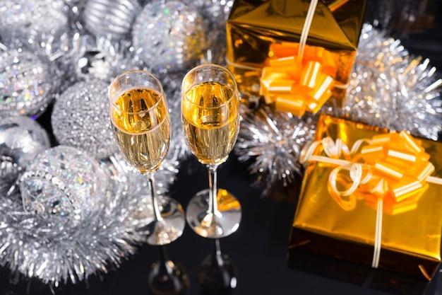 Luxuriöses weihnachtsstillleben mit zwei flöten funkelnden champagners, verzierten goldenen geschenken und einem arrangement aus silbernem lametta und weihnachtsdekorationen auf schwarzem hintergrund