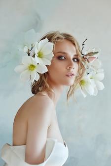 Luxuriöses weißes hochzeitskleid am körper der frau. neue kollektion von brautkleidern. morgenbraut, eine frau, die auf den bräutigam vor der hochzeitszeremonie wartet. junge braut in einem langen kleid