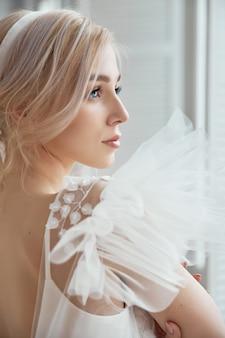 Luxuriöses weißes hochzeitskleid auf dem körper des mädchens. neue kollektion von brautkleidern. morgenbraut, eine frau, die vor der hochzeitszeremonie auf den bräutigam wartet. junge braut in einem langen kleid