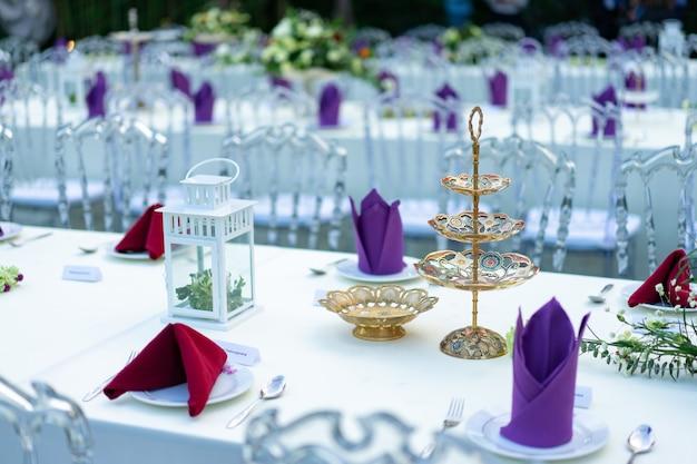 Luxus esstisch in weiß - lila - rot mit kristallstuhl im garten.