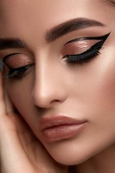 Luxus-frauen-make-up mit goldenem schatten und schwarzem eyeliner