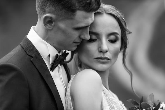 Luxus-hochzeitspaar, das das umarmen und küssen im sonnigen licht umarmt. wunderschöne braut und stilvoller bräutigam im sinnlich zarten emotionalen moment. schwarzweiss-foto.