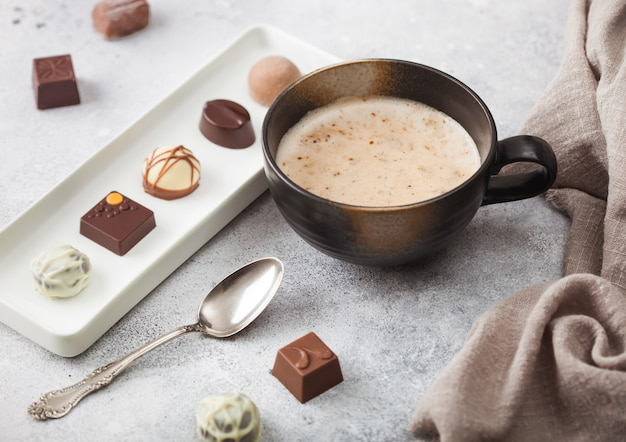 Luxus-pralinen in weißem porzellanteller mit tasse cappuccino-kaffee und silbernem löffel
