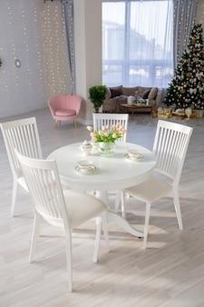 Luxus reiches teures apartment interieur in hellen farben. stilvolles, zeitgemäßes, minimalistisches design. voller sonnenlicht. viel platz mit weihnachtsbaum geschmückt