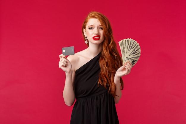 Luxus-, schönheits- und geldkonzept. unentschlossene und unsichere, gut aussehende junge rothaarige freundin, die viel geld und kreditkarte in der hand hält und unsicher verzieht, hat zweifel, wie viel es verschwendet