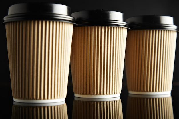 Luxus-set aus braunen pappbechern zum mitnehmen, geschlossen mit kappen, die auf schwarz isoliert und verspiegelt sind. einzelhandelspräsentation