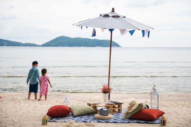 Luxus-strandpicknick mit champagner und essen unter sonnenschirm, während kinder, älterer bruder und kleine schwester, auf weißem sand in phuket, thailand stehen. familienurlaub im sommer.