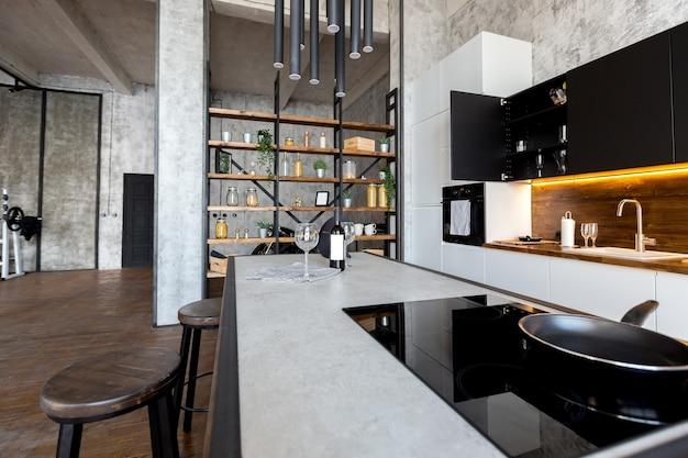 Luxusapartment im loftstil in dunklen farben. stilvoller moderner küchenbereich mit einer insel