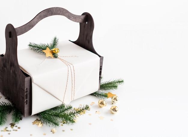 Luxusgeschenk des neuen jahres mit golddekoration und baumasten. weihnachtsgeschenk im hölzernen korb. weihnachtshintergrund mit geschenkbox. geschenke zur weihnachtsfeier.