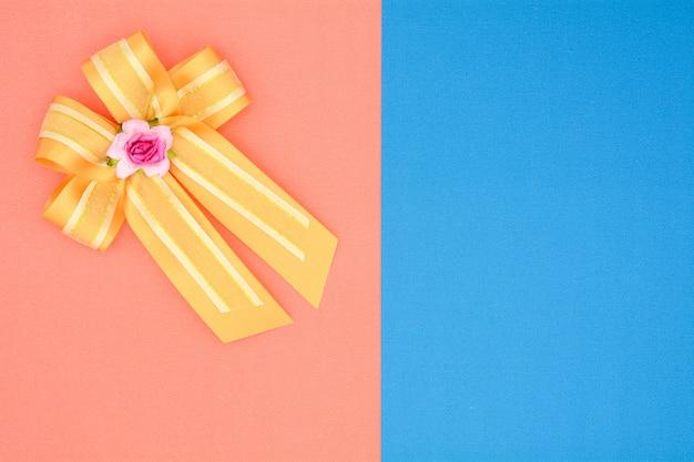 Luxusgoldsatinband auf rosa und blauem hintergrund