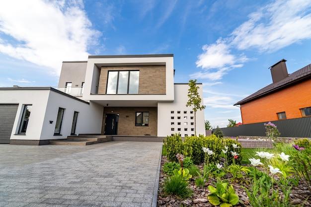 Luxushaus mit garage. blauer himmel oben. niemand im hof. moderne architektur. gemütliches und modernes haus. moderne architektur.