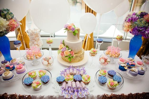 Luxushochzeitsverpflegung, tabelle mit modernen nachtischen, kleine kuchen, bonbons mit früchten.