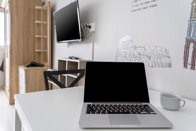 Luxusinnenwohnzimmer mit dem arbeitsplatz, der mit technologielaptop arbeitet