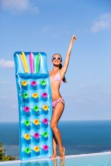 Luxusleben, sommerporträt im urlaubsstil einer glücklichen jungen frau mit gebräuntem, schlankem körper, sonne in der luxusvilla, luftmatratzen auf ihren händen haltend.