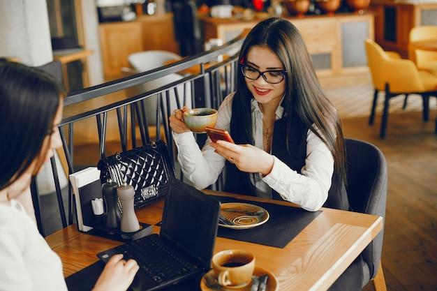 Luxusmädchen zwei, das in einem restaurant sitzt