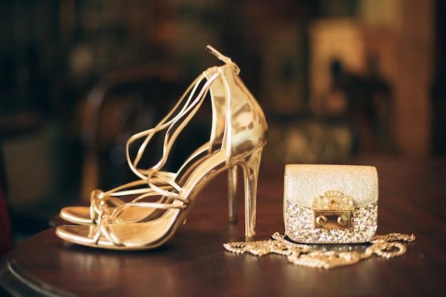 Luxusmode damenaccessoires, goldene stöckelschuhe, kleine abendtasche, eleganter stil, vintage-stil, sandalenschuhe