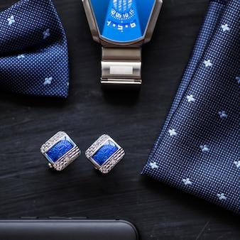 Luxusmode für männer accessoires manschettenknöpfe schmetterlings-stil uhr und smartphone nahaufnahme