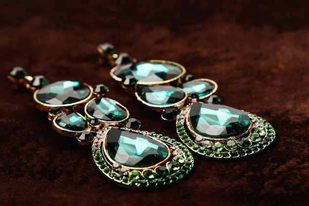 Luxusohrringe mit grünen edelsteinen auf dem braunen samt