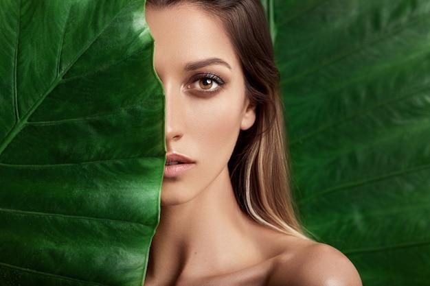 Luxusporträt einer schönen jungen frau mit natürlichem make-up hält ein großes grünes blatt