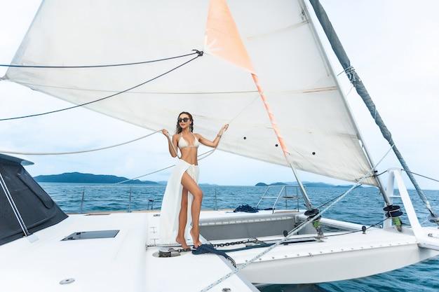 Luxusreiseyacht. junge frau, welche die sonnigen tage auf der segeljacht das meer genießt.