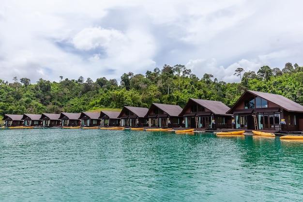 Luxusresort mit schwimmenden floßhäusern am grünen see mit tropischen bäumen