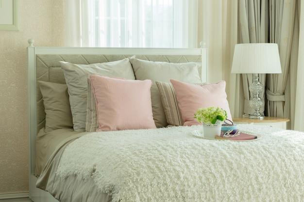 Luxusschlafzimmerinnenraum mit rosa kissen und weißem behälter der blume auf bett