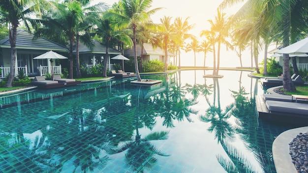 Luxusschwimmbad vor privaten tropischen landhäusern im hotel