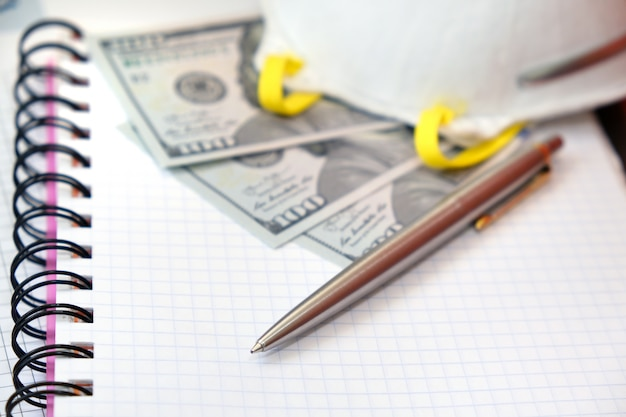 Luxusstift, schutzmaske und us-dollar-banknoten