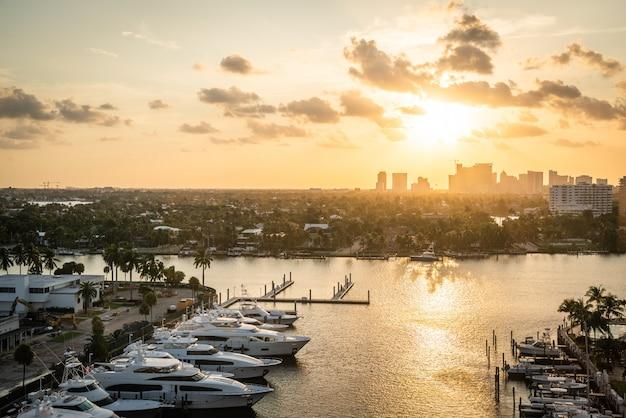 Luxusyacht geparkt an einem kanal mit sonnenuntergang in fort lauderdale. hafen von fort lauderdale mit sonnenuntergang am jachthafen