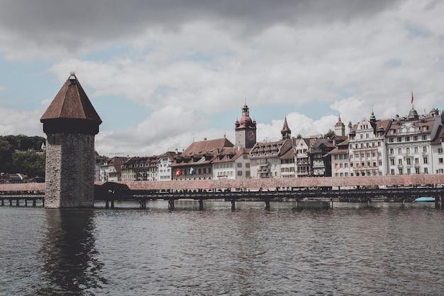 Luzern, schweiz - 3. juli 2017: panoramablick auf das stadtzentrum von luzern mit der berühmten kapellbrücke und dem fluss reuss. sommerlandschaft, sonnenscheinwetter, dramatischer himmel und sonniger tag