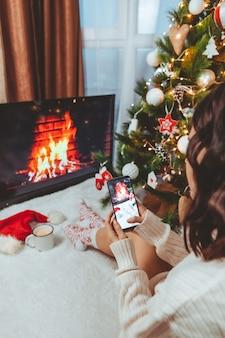 Lviv, ukraine - 15. dezember 2021: junge hübsche frau sitzt in der nähe des weihnachtsbaums und trinkt eine tasse kaffee