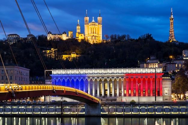 Lyon-frankreich 19. november 2015: das historische gerichtsgebäude von lyon mit den farben der französischen flagge mit basilika von fourviere über der saone im hintergrund bei sonnenuntergang.