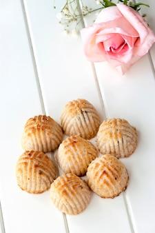 Maamoul traditionelles arabisches gefülltes gebäck oder plätzchen mit datteln oder cashewnüssen oder walnüssen oder mandeln oder pistazien. östliche süßigkeiten. nahansicht. ramadan-konzept des weißen hölzernen raumes.