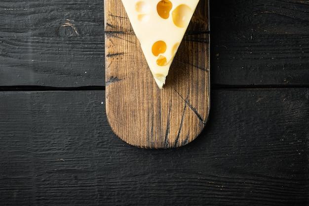 Maasdam-käse auf schwarzem holz