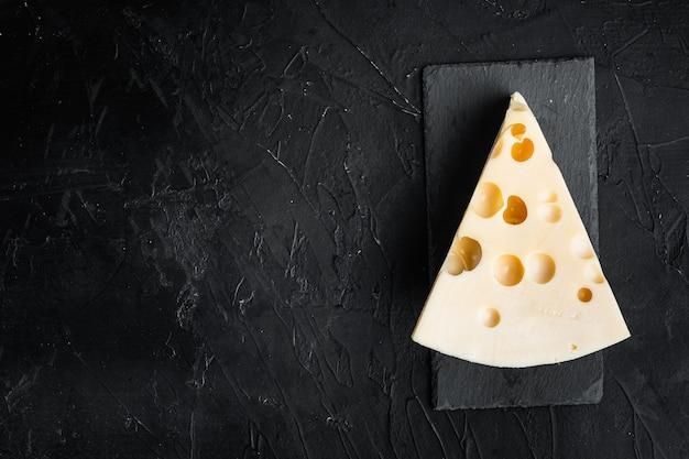 Maasdam-käse auf schwarzem stein